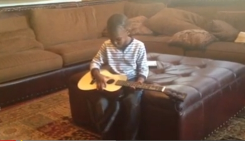 child singing with acoustic guitar